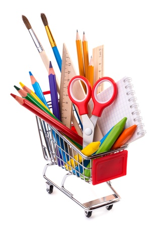 School supplies: assorted crayons, paintbrushes, pencils, pastels, rulers and notebook in a shopping cart, isolated on white background   photo
