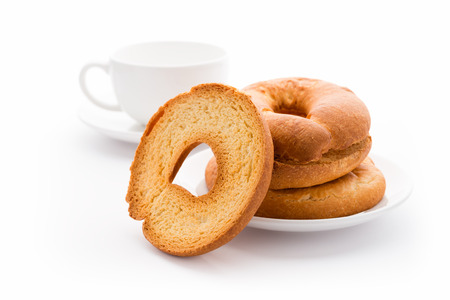 Bread and bakery: high key image of toasted bagels on a plate and tea cup, isolated photo