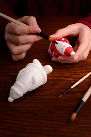 Christmas decorations: woman hands with porcelain figurine of Santa, painting, making of Christmas decoration photo