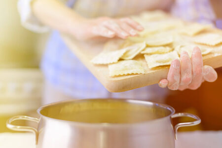 Cooking: woman hands holding fresh ravioli over the saucepan, sunlight effect added Stock Photo