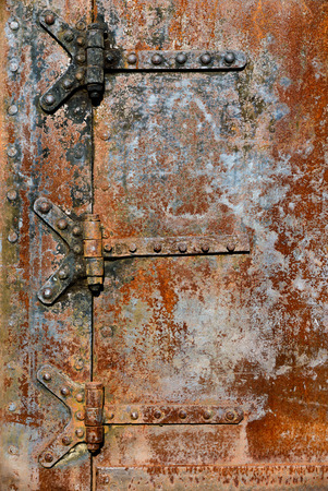 hinge joint: Backgrounds and textures: rusty metal door surface with riveted hinges, industrial abstract