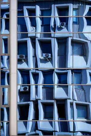 Textures and backgrounds: distorted reflection in blue glass building wall, architecture abstract Stock Photo
