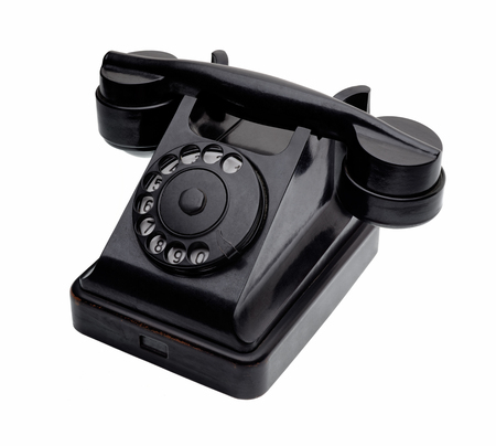 20th century: Isolated objects: old black telephone, middle of 20th century, aged and scuffed, isolated on white background