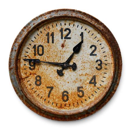 Muy viejo reloj de pared redondo desgastado y oxidado, aislado sobre fondo blanco. Foto de archivo