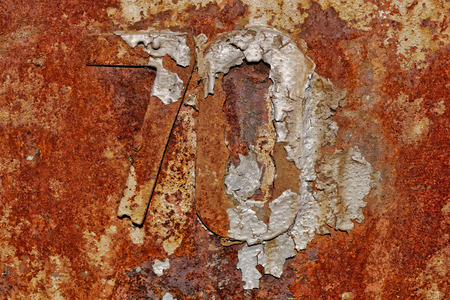 Backgrounds and textures: very old rusty metal wall surface, with number 70, industrial abstract
