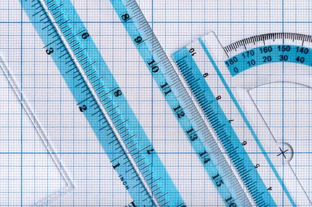 Arrière-plans et textures : groupe de règles en plastique transparent, disposées sur papier millimétré, résumé pédagogique