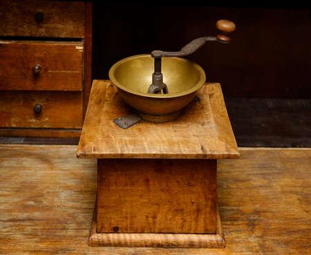 Antique aged manual wooden coffee grinder, kitchen interior, old drawer closet at background