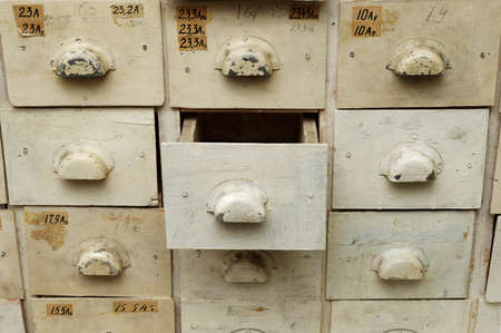 Backgrounds and textures: old wooden cabinet with drawers, one drawer opened, close-up shot