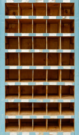 Backgrounds and textures: very old stained and weathered wooden cabinet with empty open compartments, front view, close-up shot