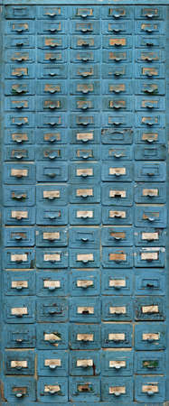 Backgrounds and textures: blue metal cabinet with drawers, very old, crooked, corroded and shabby, front view, close-up shot