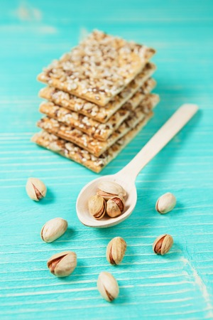 Pistachios on wooden spoon and biscuits with assorted seeds over wooden vintage background.
