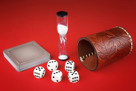 Dice, cards and leather cup on red background.