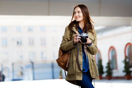 Beautiful young woman using vintage photo camera on the railway station platform. Stock Photo