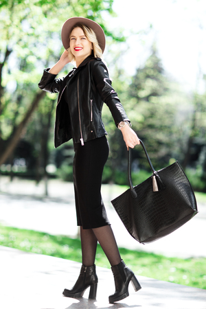 Street portrait of glamour sensual young stylish lady wearing trendy fall outfit. Blonde woman in black hat, leather jacket and bag.