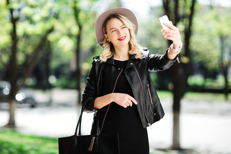 Blonde woman in black hat and leather jacket and bag using the mobile phone. Young woman taking selfie.
