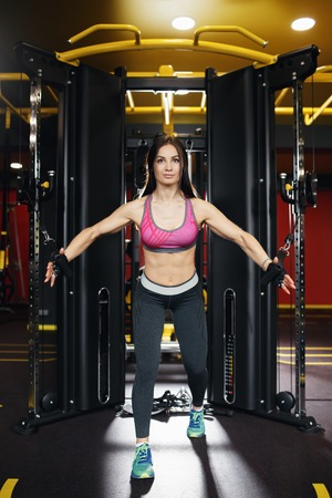 Athletic young woman doing exercise on the chest in the crossover in the gym.