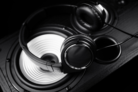 Photo of black headphones on music audio speaker. Close-up. Stock Photo