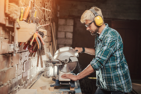 Young hipster bearded man with ear protectors by profession carpenter builder saws with a circular saw a wooden board on a wooden table in the workshop. Stockfoto
