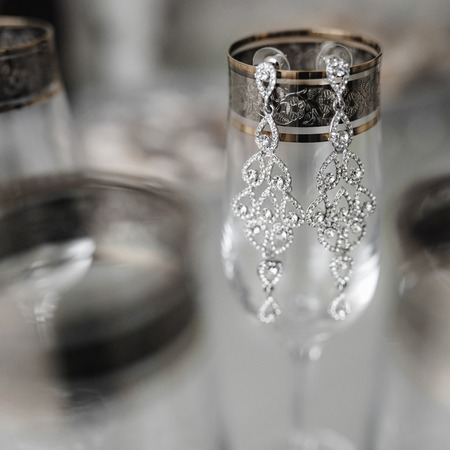 Composition of bride earrings on the vintage stylish glasses. Stock Photo