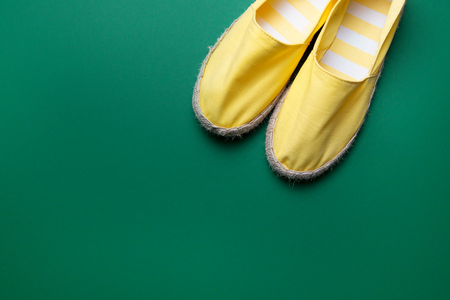 Pretty yellow summer shoes on the green background. Espadrilles.