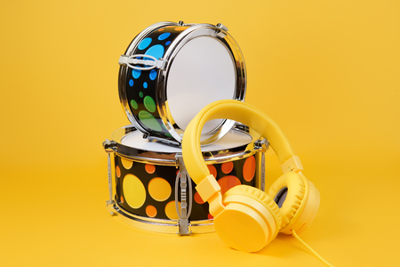 Yellow headphones and mini drum kit on the yellow background. Toy drums.