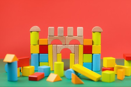 Different color and shape wooden toy blocks on colorful background.
