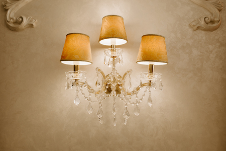 Photo of vintage crystal chandelier in the restaurant. Lamp on the wall.
