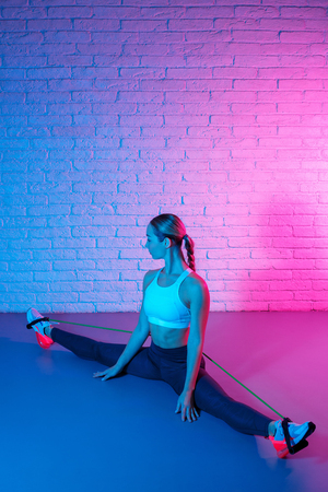 Tender young slim gymnast woman in sports clothing stretching with elastic band in front of brick wall in neon lights. Flexible muscular woman doing gymnastic split. Imagens