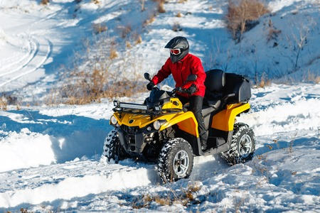 Attractive young man in red warm winter clothes and black helmet on the ATV 4wd quad bike stand in heavy snow with deep wheel track. Moto winter sports.
