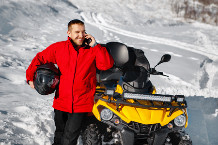 Young man driver in red warm winter clothes and black helmet talking on smartphone near the ATV 4wd quad bike stand in heavy snow with deep wheel track. Moto winter sports. Imagens