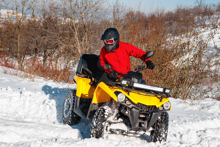 Photo of young extremal driver in red warm winter clothes and black helmet jump in the air with the ATV 4wd quad bike stand in heavy snow with deep wheel track. Extreme moto winter sports.