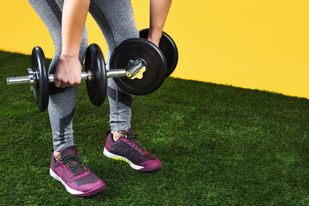 Close up photo of handsome fit young woman legs exercises with dumbbells on the green grass over yellow background. 版權商用圖片