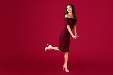 Full lengh portrait of elegant young woman in maroon dress over red background. Stock Photo