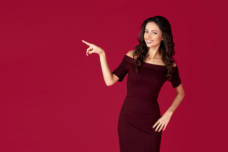Photo of elegant young woman in maroon dress point fingers away over red background.