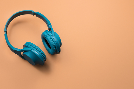 Photo of stylish modern blue cyan headphones over beige background