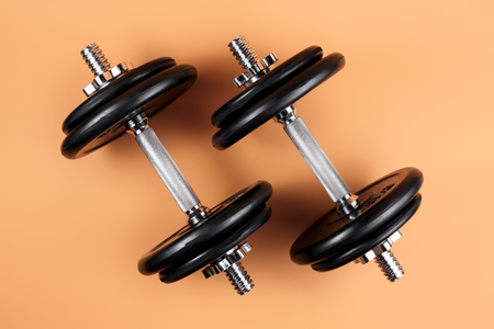 Professional dumbbell and weight plates over beige background. Black metal dumbbell with chrome silver handle. Gym equipment. Fitness concept.