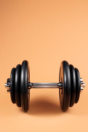 Mancuernas profesionales y placas de peso sobre fondo beige. Mancuerna de metal negro con mango plateado cromado. Equipo de gimnasio. Concepto de fitness