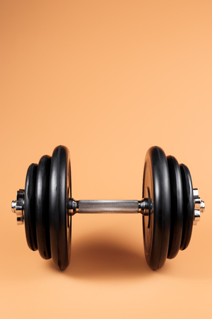 Professional dumbbell and weight plates over beige background. Black metal dumbbell with chrome silver handle. Gym equipment. Fitness concept