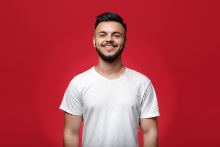 Pretty young bearded hipster in white t-shirt over red background. Bright smile. White teeth