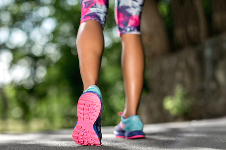 Woman fitness sunrise jog workout welness concept. Runner feet running on road closeup on shoe.