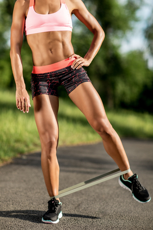 Close-up photo of young sporty woman legs doing exercises with rubber band outdoor.
