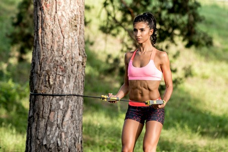 Attractive fitness young woman exercising with resistance band oudoor.
