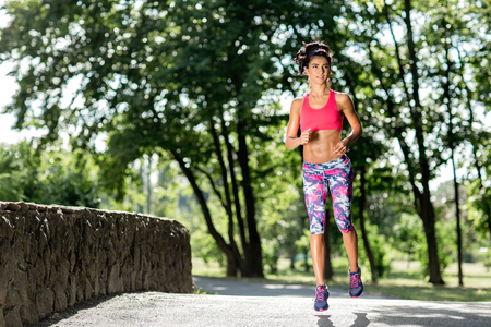 Young female runner jogging during outdoor workout in a park. Beautiful fit girl. Weight Loss. Sport LIfestyle.