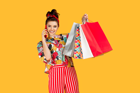 Attractive young caucasian woman in casual colorful clothes holding bags and shopping and talk on smartphone over orange background. Shopping and sales concept. Stok Fotoğraf