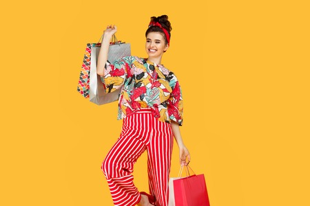 Charming young caucasian woman in casual colorful clothes holding bags and shopping over orange background. Shopping and sales concept. Stok Fotoğraf