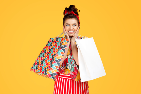 Shocked young caucasian woman in casual colorful clothes holding bags and shopping over orange background. Shopping and sales concept. Stok Fotoğraf