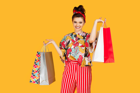 Young happy caucasian woman in casual colorful clothes holding bags and shopping over orange background. Shopping and sales concept.