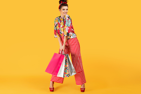 Full lenhts photo of young happy caucasian woman in casual colorful clothes holding bags and shopping over orange background. Shopping and sales concept.