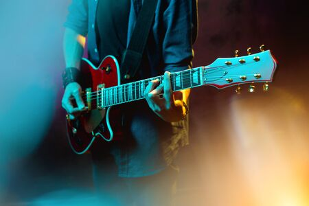 Close-up photo of hipster man with red guitar in neon lights. Rock musician is playing electrical guitar. 写真素材