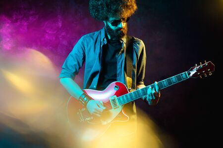 Young hipster man with curly hair with red guitar black sunglasses in neon lights. Rock musician is playing electrical guitar.